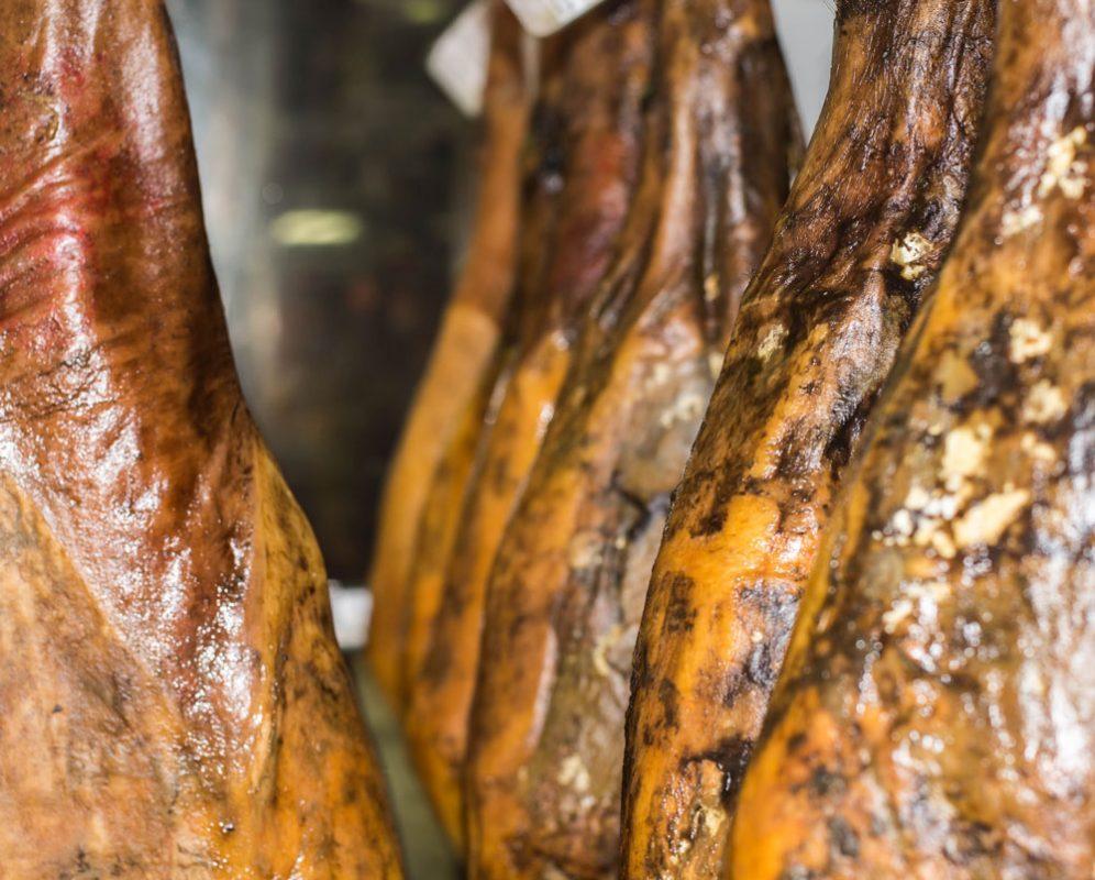 Detalle de jamones ibéricos puros de bellota colgados en el secadero